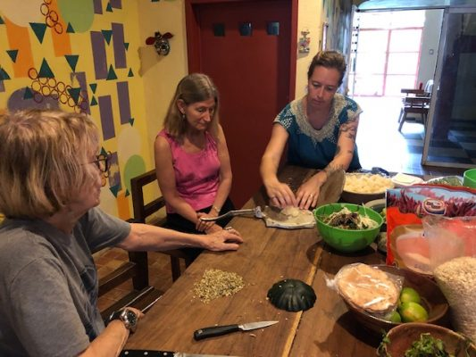 Women learn how to use tortilla press at a cooking class in Merida, Yucatan